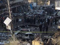Iraqi security forces inspect a crater caused by a car bomb attack in the neighborhood of Karrada in Baghdad.