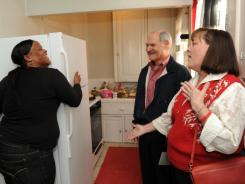 Monique McDonald hugs her refrigerator after Janis Farquhar and John Russo present it.