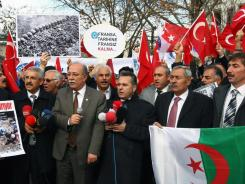 Members of a Turkish union hold Turkish and Algerian flags as they protest against France outside the French Embassy in Ankara, Turkey, on Thursday.