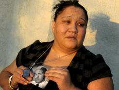 Suzanne Sullivan holds a photo of her son, Christopher Sullivan, an Army soldier, outside her home in San Bernardino, Calif., on Saturday.