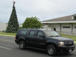 President Obama rides in his motorcade past a Christmas tree Saturday after playing golf in Kaneohe, Hawaii.