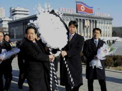 Moon Hyung-jin, president of the Unification Church, second from right, carries a wreath to lay in front of a portrait of the late Kim Jong Il Saturday at Kim Il Sung Square in Pyongyang.