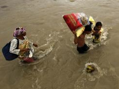 Flood victims cross a river after receiving relief goods on Christmas Day in Iligan city in the Philippines.