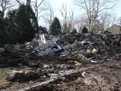 Rubble left after the demolition of a house where a fire left five people dead Christmas Day lies on the ground on Monday.