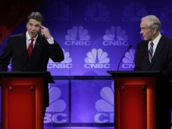 Presidential candidate Rick Perry points to his head as he speaks during a Republican presidential debate in Auburn Hills, Mich., on Nov. 9. At right is rival Ron Paul.