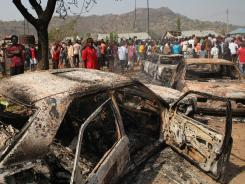 People gather around burned cars near St Theresa Catholic Church after a bomb blast in Nigeria on Christmas.
