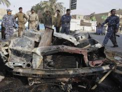 Iraqi security forces and spectators gather at the scene of a car bombing Thursday in Baghdad.
