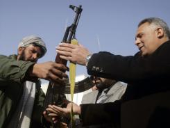 A former Taliban militant, left, hands over his weapon to Herat governor Dawood Shah Saba during a joining ceremony with the Afghan government in Herat, Afghanistan, on Wednesday.