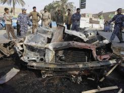 Iraqi security forces and residents gather at the scene of a car bomb attack Thursday in Baghdad.