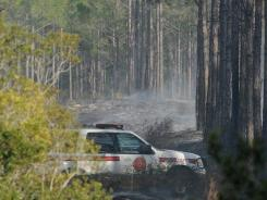 A Clay County fire official drives through smoldering brush on his way to wreckage from a helicopter crash near Green Cove Springs, Fla., on Monday.