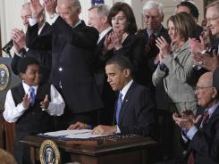 President Obama signs the health care overhaul bill into law on March 23, 2010.