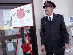 Salvation Army Lt. Sean Kelsey rings a pair of bells to collect donations outside a Cathedral City, Calif., grocery store on  Dec. 7.