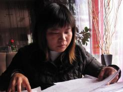 Wu Chunxia, 37, reviews the documents that she says prove she was wrongfully incarcerated in a mental hospital in central China for 132 days in 2008.