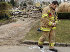 Stamford firefighter Nick Tamburro pays respects outside the home of Madonna Badger in Stamford, Conn., on Tuesday.
