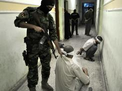 An Iraqi police officer in Fallujah, Iraq, guides a prisoner who was  accused of taking part in attacks on Shiite Muslims.