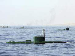 Iranian submarines and warships participate in a drill in the Sea of Oman Wednesday on Wednesday.