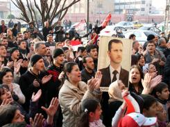 Pro-Syrian regime protesters chant slogans while one holds a picture of President Bashar Assad on Thursday in Homs, Syria.