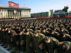 Korean People's Army officers bow at Thursday's memorial service for Kim Jong Il at the Kim Il Sung square in Pyongyang.