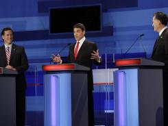 Former Pennsylvania senator Rick Santorum, Texas Gov. Rick Perry and former Massachusetts governor Mitt Romney participate in a GOP presidential debate on Dec. 15 in Sioux City, Iowa.