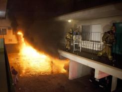 Firefighters help a man out of his apartment along with a cage of birds as multiple cars burn in a carport in the Sun Valley neighborhood of Los Angeles on Saturday.