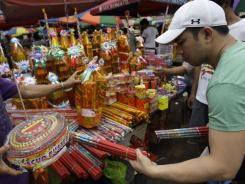 A Filipino man buys firecrackers at a makeshift stand in downtown Manila, Philippines on Saturday.