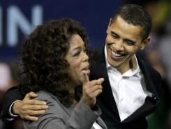 In this Dec. 9, 2007, file photo, then-Democratic presidential candidate Sen. Barack Obama, D-Ill., reacts as Oprah Winfrey introduces him to the crowd at a rally in Manchester, N.H.