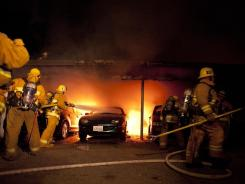 L.A. firefighters extinguish numerous cars on fire in a carport in the Sherman Oaks neighborhood of Los Angeles on Jan. 2.