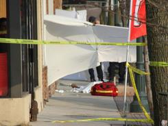 A sheet covers a body after a shooting at a pharmacy in Seaford, N.Y.