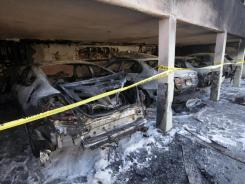 The charred remains of cars sit in a Los Angeles carport Monday. Authorities haven't said how the car fires were sparked.