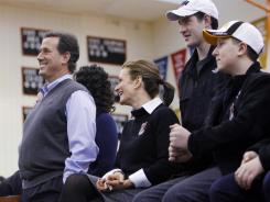 Former Pennsylvania senator Rick Santorum, left, stands with his family before speaking at a forum Tuesday at Valley High School in West Des Moines.