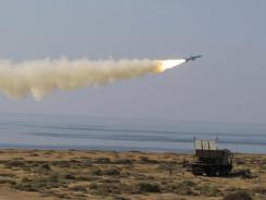 In this picture released Monday by Iranian Fars News Agency, a Ghader missile is launched at the shore of sea of Oman during Iran's navy drill.