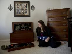 Jane Horton sits with her husband's military memorabilia in her bedroom.