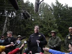 Pierce County Sheriff's detective and spokesman Ed Troyer, center, talks to reporters as Mount Rainier National Park Superintendent Randy King, second from right, and FBI Agent Steven Dean, right, look on,