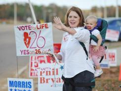Joyce Haskins, with her grandchild Landry Bruce, supports Amendment 26 outside the voting booths in Oxford, Miss. on Nov. 8.