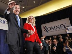 Former Massachusetts governor Mitt Romney takes the stage with his wife, Ann, at an event Tuesday night in Des Moines.
