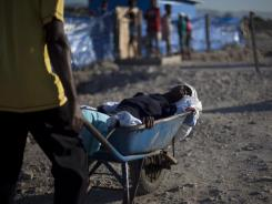 A woman suffering cholera symptoms is pushed in a wheelbarrow to a hospital Wednesday in the Cite Soleil slum in Port-au-Prince,