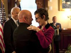 Retired astronaut Mark Kelly hugs his wife, Rep. Gabrielle Giffords, on Oct. 6 after he receives an award from Vice President Biden, left. during a White House ceremony.