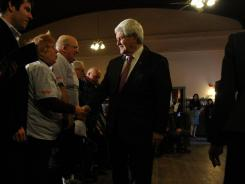 Newt Gingrich greets Kathy and Chuck Engborg of Ashland, N.H., at the Plymouth (N.H.) Regional Senior Center on Thursday.