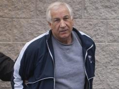 Former Penn State football coach Jerry Sandusky is escorted by state police Dec. 7.