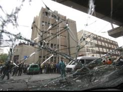 A Syrian police station building, background, seen through a smashed car windscreen soon after an attack by a suicide bomber, in Damascus' Midan neighborhood Friday.