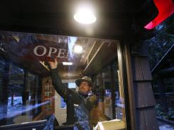 "Mount Rainier National Park Ranger Matt Chalup turns around the sign to read ""open"" Saturday morning. The park opened for the first time since the shooting death of Ranger Margaret Anderson on Jan. 1."