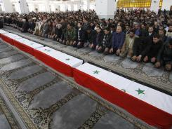 Syrian mourners pray in front of the coffins of 11 Syrian police officers who were killed in an explosion in Damascus on Friday.