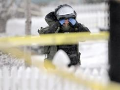 A member of the Boulder County Bomb Squad responds to an explosion inside a car on Saturday in Lafayette, Colo. Two people inside the car were seriously injured.