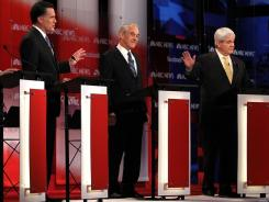 Former Massachusetts governor Mitt Romney, Texas Rep. Ron Paul and former House speaker Newt Gingrich participate in Sunday's GOP presidential debate in Concord, N.H.
