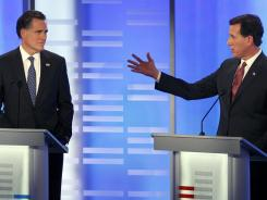Former Massachusetts governor Mitt Romney, left, listens as former Pennsylvania senator Rick Santorum answers a question during a Republican presidential debate Saturday in Manchester, N.H.