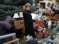 Julie Holzhauer looks over an old family photo album found in her household possessions spread over the front lawn after being evicted on Sept. 15, 2011, in Centennial, Colo.