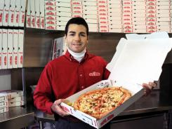 Papa John's Pizza founder John Schnatter shows off a pizza at a store in Louisville, Ky. The company is apologizing after an employee typed a racial slur on a receipt.