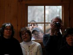 People look through a window over the shoulders of others listening to Rick Santorum on Saturday in Hollis, N.H.