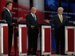 Former Massachusetts governor Mitt Romney, left, Texas Rep. Ron Paul and former House speaker Newt Gingrich take part in Sunday morning's GOP presidential debate in Concord, N.H.