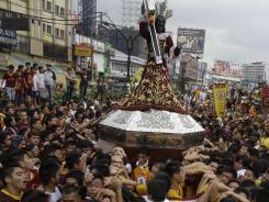 A replica of a centuries-old black statue of Jesus Christ, known as the Black Nazarene, is carried by devotees during the blessing and procession of the replicas in Manila.